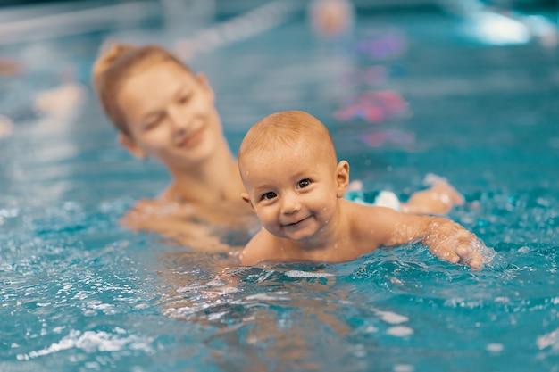 Giovane madre e il suo bambino godendo di una lezione di nuoto per bambini in piscina. bambino che si diverte in acqua con la mamma