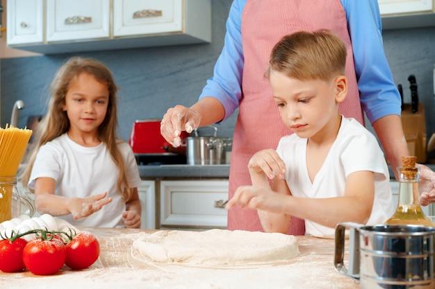 Giovane madre e i suoi bambini carini che cucinano pizza insieme in cucina