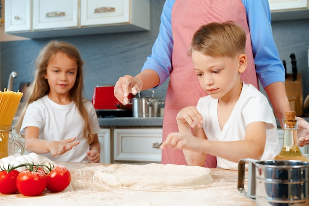 Giovane madre e i suoi bambini carini che cucinano pizza insieme
