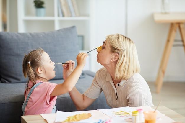 La giovane madre e sua figlia dipingono di fronte a vicenda con il pennello e le vernici nel soggiorno