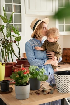 La giovane madre e suo figlio sono impegnati nella coltivazione di fiori domestici a casa