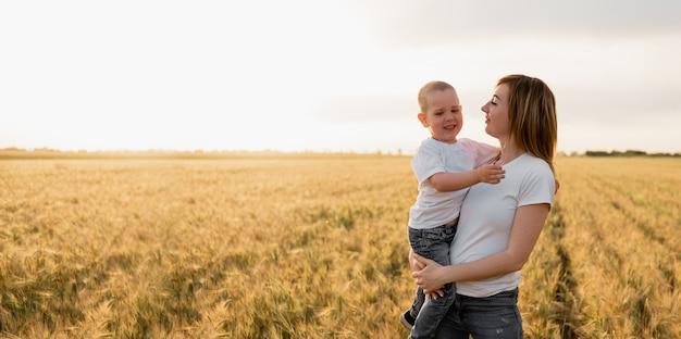 Giovane madre che tiene il suo bambino in braccio in un campo di grano