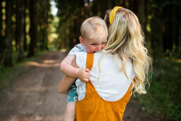 Giovane madre che tiene il suo figlio che piange nella foresta