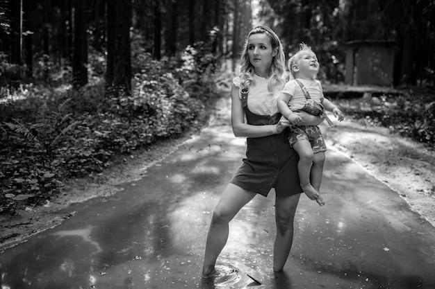 Giovane madre che tiene il suo figlio che piange e in piedi nella pozzanghera nella foresta