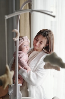 Giovane madre che tiene in braccio la sua graziosa bambina in abiti rosa