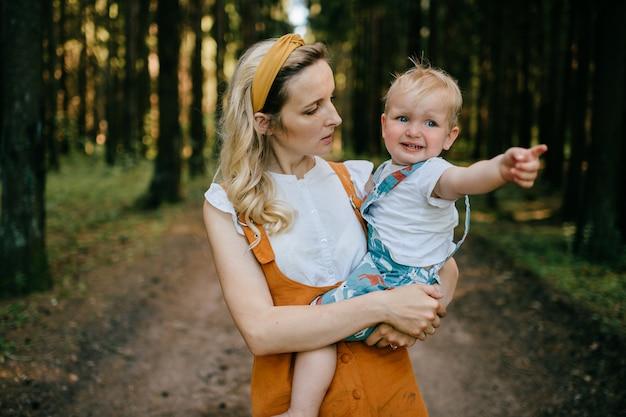 Giovane madre che tiene il suo figlio divertente nella foresta