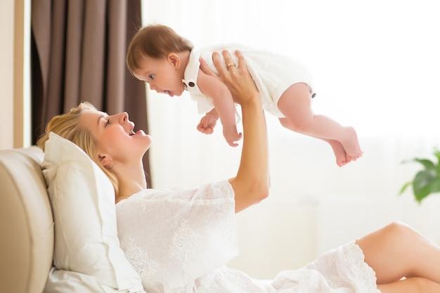 Giovane madre che tiene il suo bambino appena nato. bambino che allatta mamma felice. donna e neonata insieme in una camera da letto bianca a casa. bambino di allattamento al seno della madre. stile di vita familiare