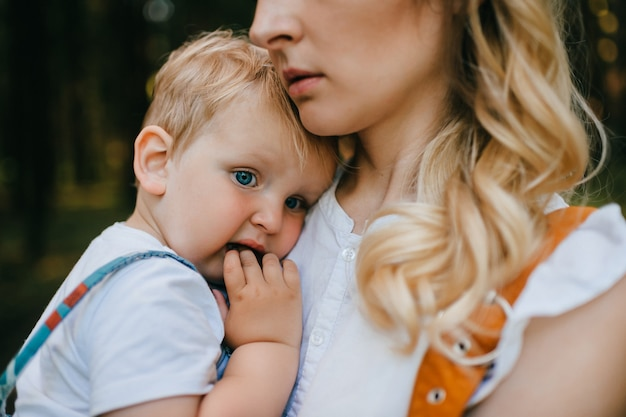 Giovane madre che tiene suo figlio nella foresta