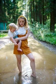 Giovane madre che tiene suo figlio e in piedi nella pozzanghera nella foresta