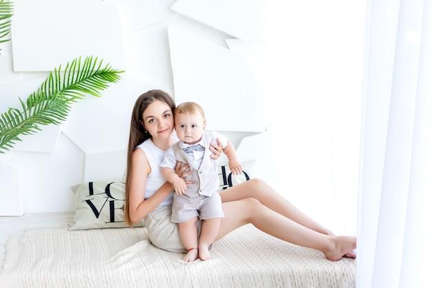 La giovane madre tiene il figlio neonato 1 anno, la festa della famiglia, la festa della mamma