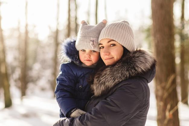 La giovane madre tiene la piccola figlia del bambino tra le braccia in inverno nel parco
