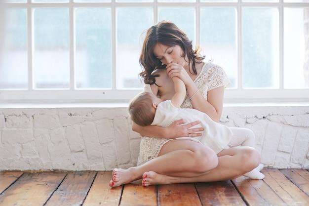 La giovane madre sta allattando il suo bambino a casa bella luce