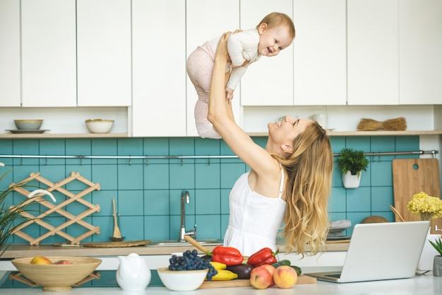 La giovane madre sta cucinando e giocando con sua figlia in una cucina moderna.