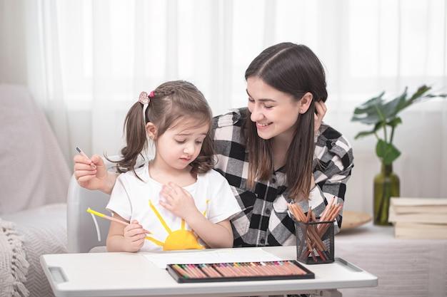 La giovane madre sta facendo i compiti con la sua piccola figlia carina. istruzione domestica e concetto di istruzione.