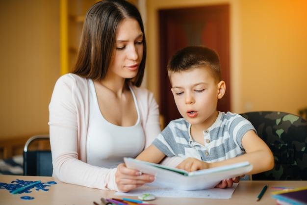 Una giovane madre sta facendo i compiti con suo figlio a casa. genitori e formazione.