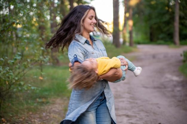 La giovane madre gira con un bambino in braccio. mamma felice che balla con il bambino sullo sfondo della natura e della foresta. mamma e figlia ridono. genitorialità spensierata
