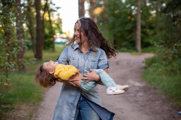 La giovane madre gira con un bambino in braccio mamma felice che balla con un bambino sullo sfondo di