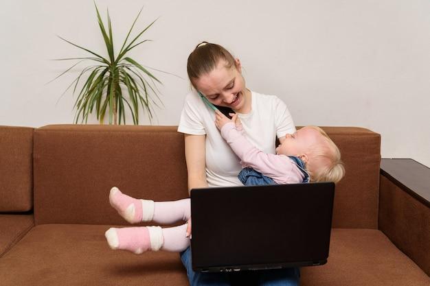La giovane madre sta parlando al telefono e tiene il bambino in braccio. concetto di donna moderna.
