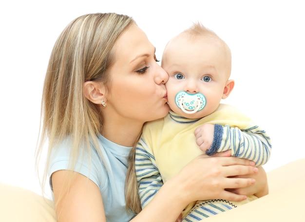 La giovane madre bacia e abbraccia il bambino