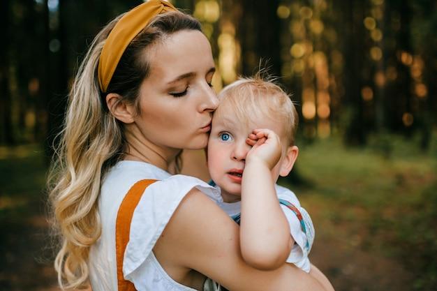 Giovane madre che bacia il figlio nella foresta