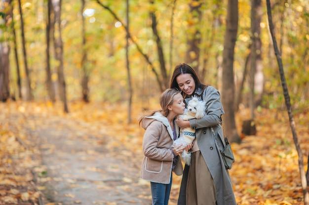 Giovane madre e bambina in autunno parcheggiano ad ottobre