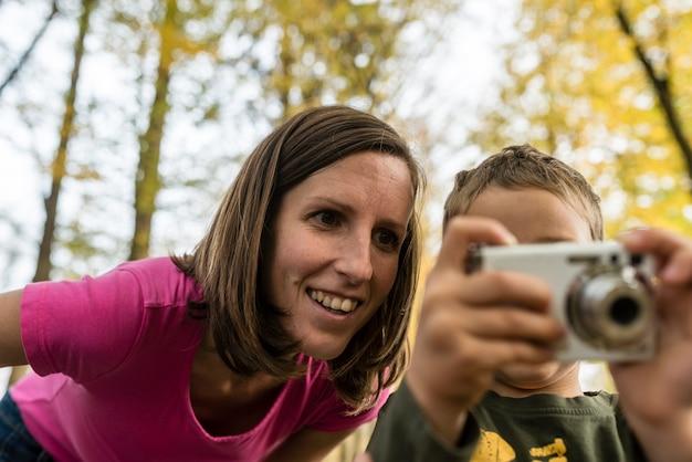 Giovane madre che guarda un'immagine su una fotocamera tenuta dal suo piccolo figlio mentre fotografa nel bosco in autunno.