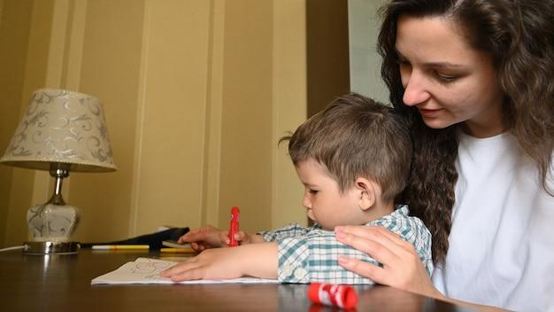 Una giovane madre dipinge con i pennarelli con un bambino.