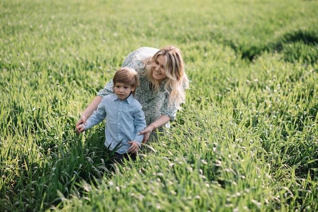 La giovane madre gioca con il figlio di 3 anni sul campo in erba, l'erba verde è alta quasi quanto il ragazzo.