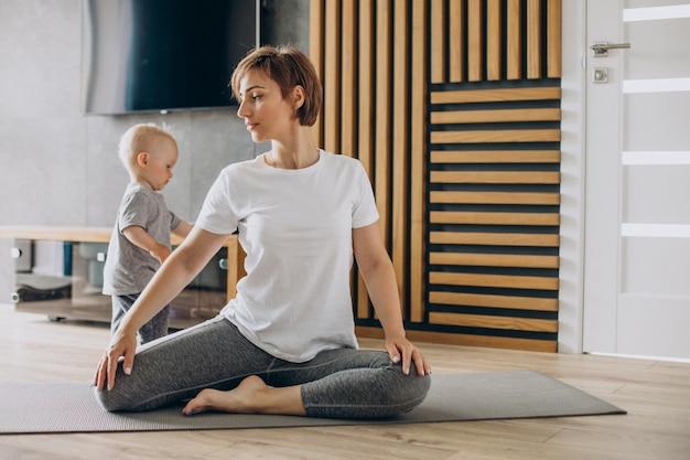 La giovane madre pratica lo yoga con il figlio piccolo sul tappetino