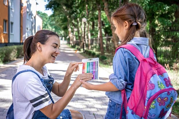 Una giovane madre vede la piccola figlia a scuola e dà loro dei pennarelli colorati.