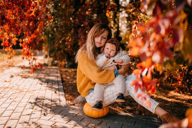 La giovane madre si siede nel parco di autunno con il suo bambino piccolo