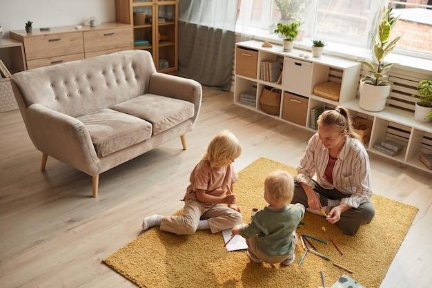 Giovane madre seduta sul tappeto insieme ai suoi figli giocano e disegnano in soggiorno