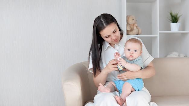 Una giovane madre seduta sul divano con un bambino in grembo guarda suo figlio che gioca con un sonaglio con lui