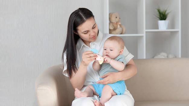 Una giovane madre, seduta sul divano con un bambino in grembo, gioca con il suo sonaglio