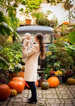 Giovane madre e figlia piccola su sfondo di zucche, vigilia di halloween