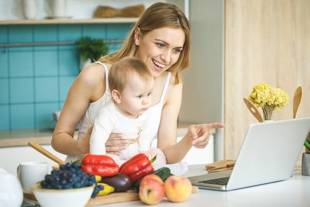 Giovane madre che sorride, che cucina e che gioca con sua figlia in una cucina moderna. usando il portatile.