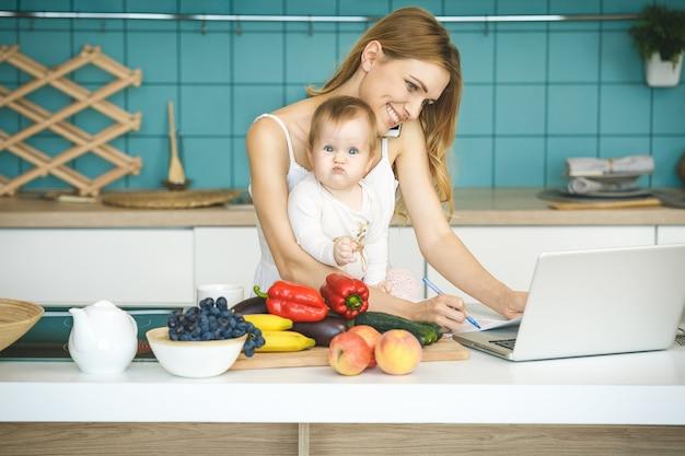 Giovane madre che sorride, che cucina e che gioca con sua figlia in una cucina moderna. usando il telefono. lavorare a casa.