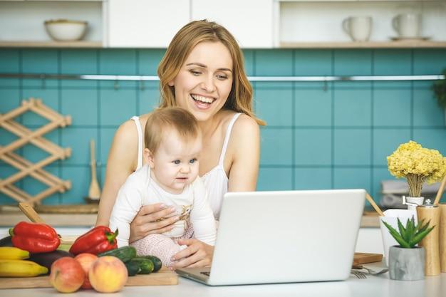 Giovane madre che sorride, che cucina e che gioca con sua figlia in una cucina moderna. usando il telefono.