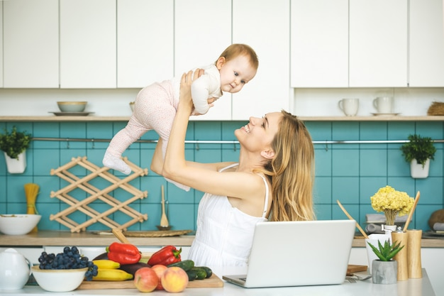 Giovane madre che sorride, che cucina e che gioca con sua figlia in una cucina moderna. lavorare a casa.