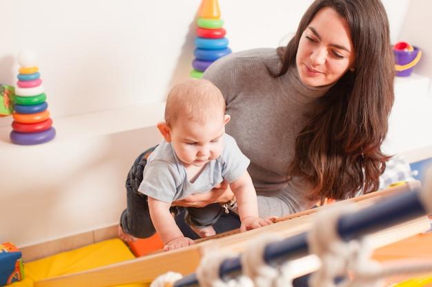 La giovane madre sostiene il bambino, aiutandolo a salire la scala all'asilo