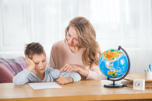 Giovane madre che insegna al suo piccolo figlio a casa. mamma e suo figlio studiano la geografia al chiuso