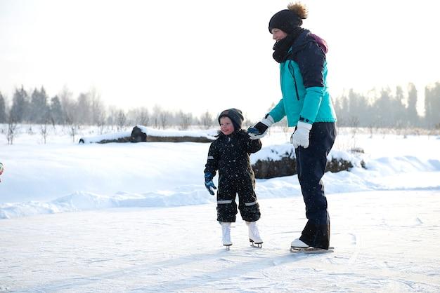 Giovane madre che insegna al suo piccolo figlio a pattinare sul ghiaccio alla pista di pattinaggio all'aperto. la famiglia si gode l'inverno sulla pista di pattinaggio sul ghiaccio all'aperto