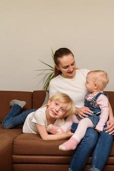 Giovane madre e due bambini seduti sul divano. concetto di famiglia felice. cornice verticale.