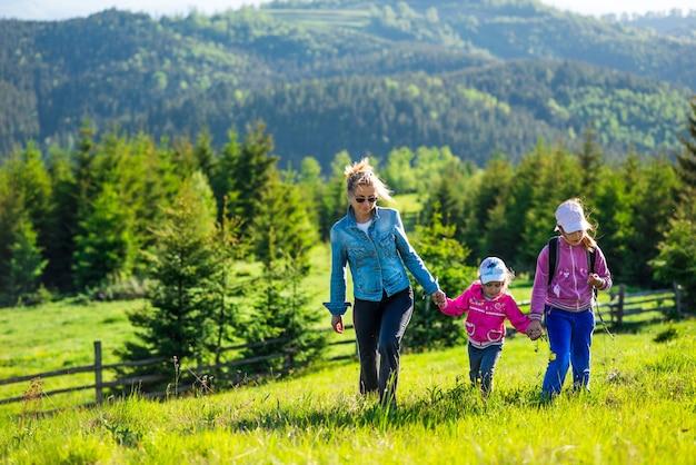 Giovane madre e due piccole figlie viaggiatori stanno su un pendio con una splendida vista sulle colline ricoperte da una fitta foresta di abeti contro il cielo blu