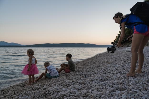 Giovane madre che utilizza un supporto cardanico per riprendere i suoi tre bambini che giocano al tramonto sulla spiaggia di ciottoli in riva al mare.