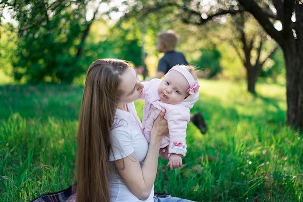 Giovane madre che cammina con un bambino piccolo nel parco. concetto di bambino e genitorialità