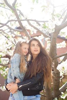 Giovane madre con figlia adorabile nel parco con albero in fiore