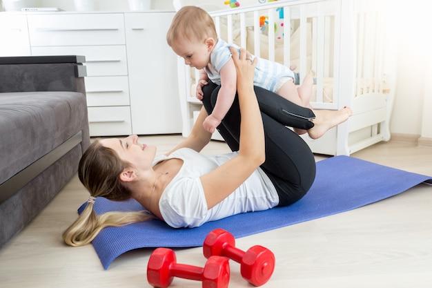 Giovane madre con bambino che fa esercizio di yoga sul pavimento in soggiorno