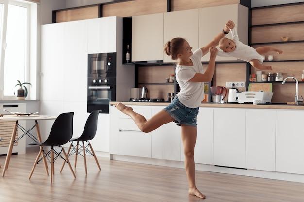 La giovane madre con il bambino si diverte in cucina a casa