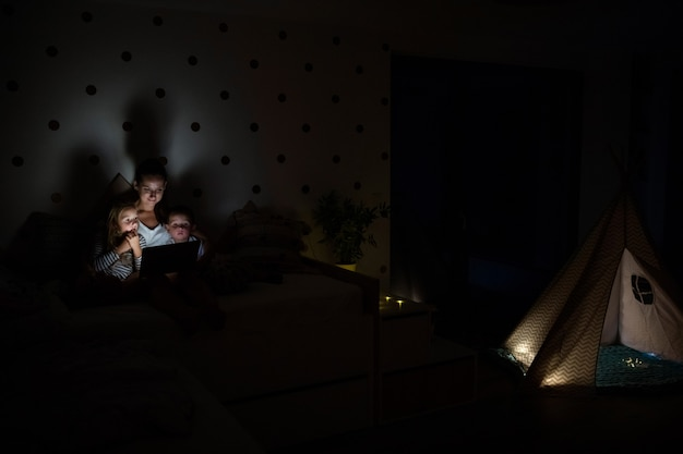 Giovane madre con bambini seduti al chiuso in camera da letto la sera, utilizzando il computer portatile.